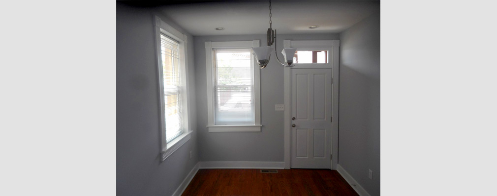 Photograph of a room in a rehabilitated rowhouse with wood flooring, wood-framed windows and a hanging light fixture.