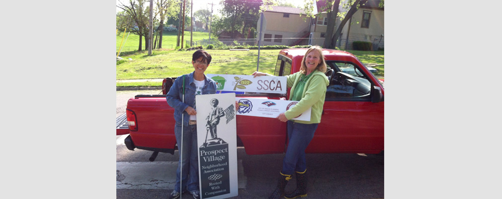 "Photograph of two women in front of a pickup truck holding three organizational signs, including one that reads, ""Prospect Village Neighborhood Association: Rooted with Compassion."""