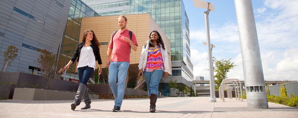 Photograph of three students walking in front of a multistory academic building.