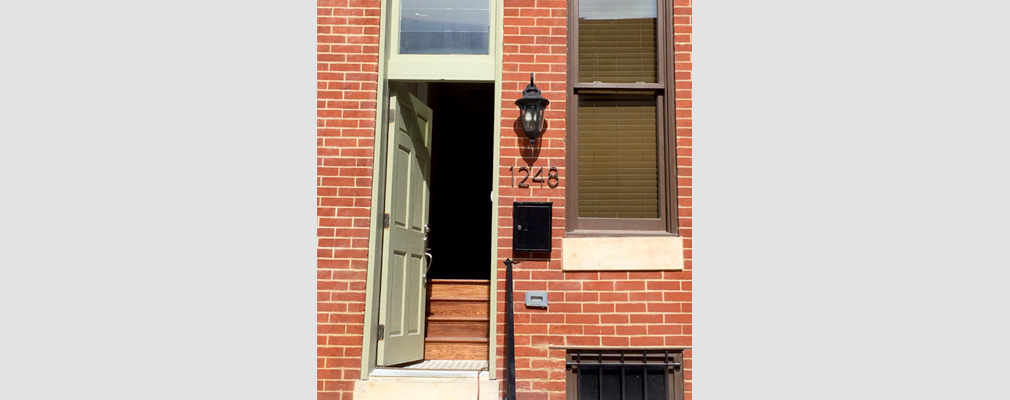 Photograph of the entrance to a renovated brick rowhouse.