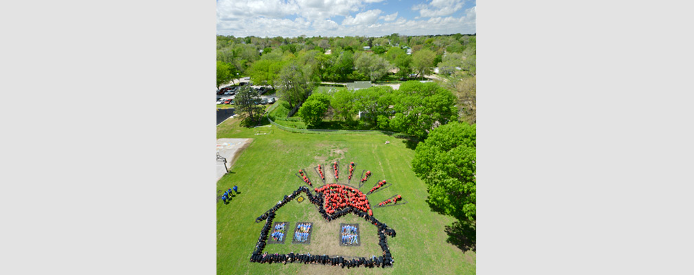 Low-altitude aerial photograph of Franklin Elementary School students in red, blue, and black shirts, lying on the ground in the shape of a house and a rising sun for the Art for the Sky project.