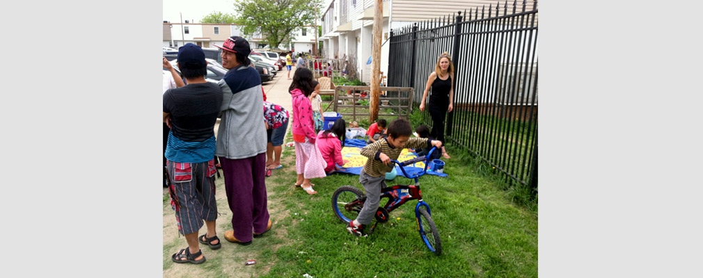Photograph of children and adults enjoying an outdoor gathering in a housing development.