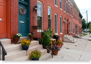 Photograph of several rehabilitated two-story brick rowhouses.
