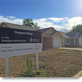 "Photograph of the front façades of three newly constructed houses, with a sign in the foreground reading ""Prospect Village: financed by American National Bank partnering with Holy Name Housing Corporation."""