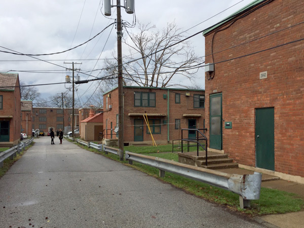 Image showing rows of brick, multifamily housing units along a street.