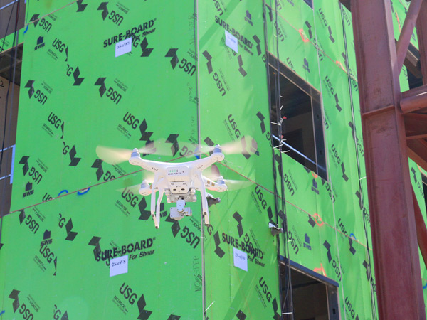 Image of a drone flying in front of a building under construction.