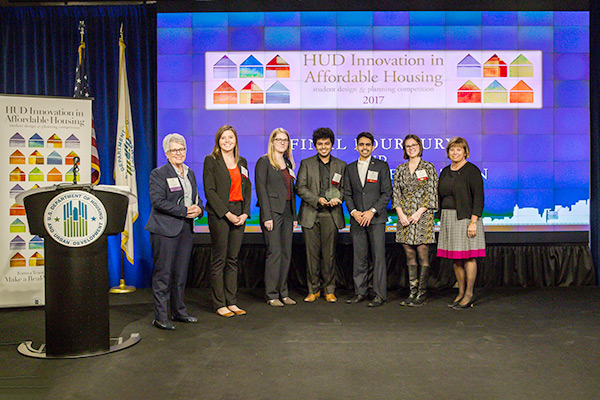 The University of Michigan at Ann Arbor team and HUD Acting Deputy Secretary Janet Golrick stand in front of the 2017 Innovation in Affordable Housing background.
