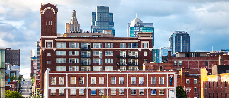 Photograph of several multi-story brick buildings in front of the Kansas City, Missouri skyline.