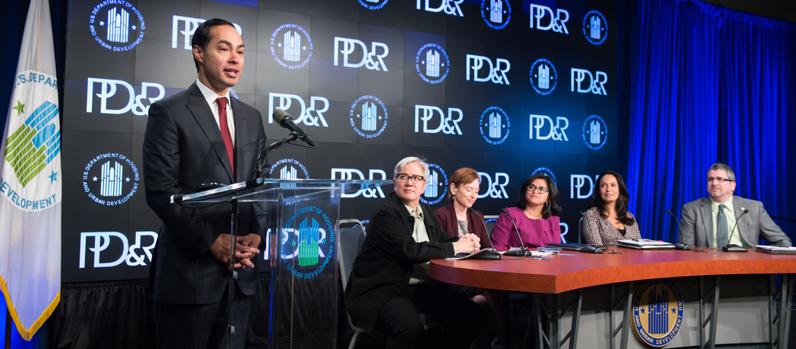 Photograph of HUD Secretary Julián Castro speaking at a podium in front of a background with the PD&R logo.