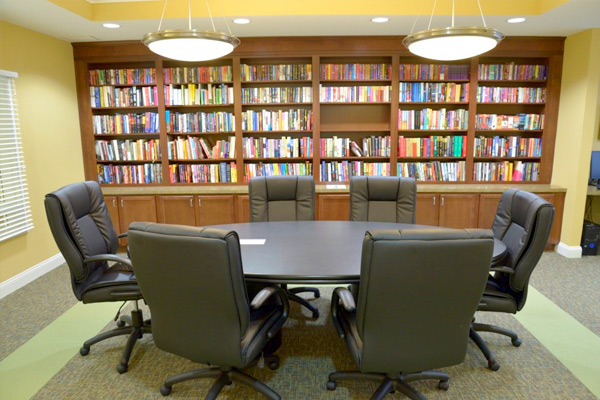 Photograph of a room with a conference table and seating in front of a wall of book-lined shelves.