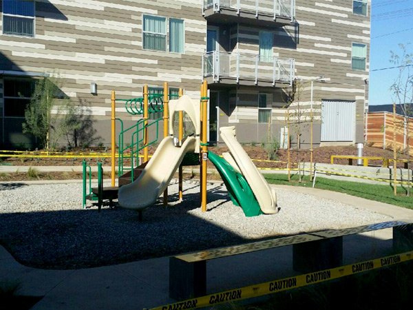 Photograph of a playground adjacent to a multistory residential building.