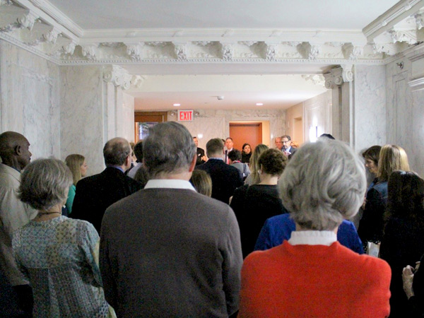 Photograph of approximately two dozen neighbors, residents, and other interested people standing in an ornate marble lobby during the ribbon-cutting ceremony.