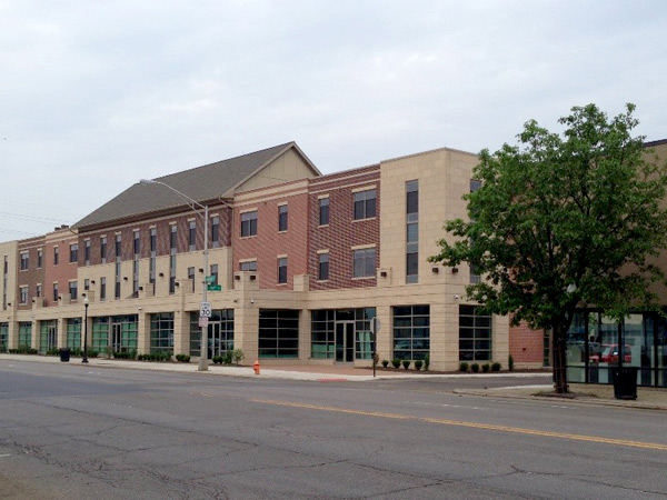 Photograph of the front façade of a three-story mixed use building along a commercial street.