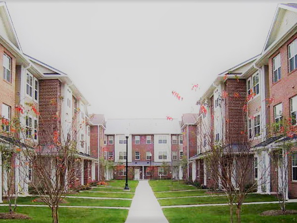 Photograph of a courtyard with three-story residential buildings on three sides.
