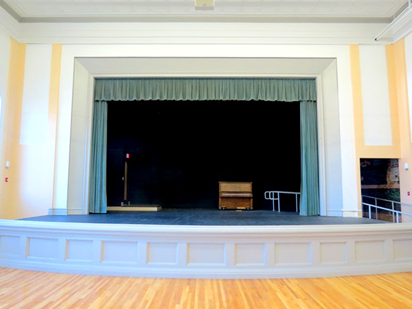 Photograph of a proscenium stage at one end of an auditorium with a wooden floor.