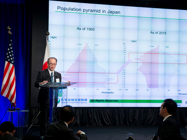 Image of a man standing behind a podium in front of a screen with two charts displaying the distribution of the population of Japan by age in 1965 and 2015.