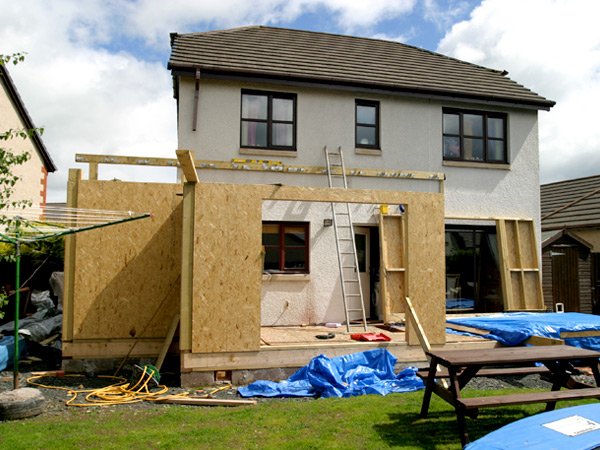 Photograph of the back of a detached single family home undergoing renovation.