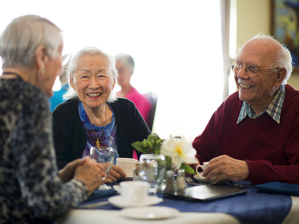 Two older women and a man sit around a small table drinking coffee.