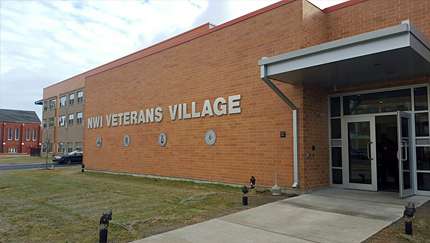 "Photograph of the front door and façade of a one-story, flat-roofed building with a wall sign reading, ""NWI Veterans Village""; a three-story residential wing is in the middle ground."
