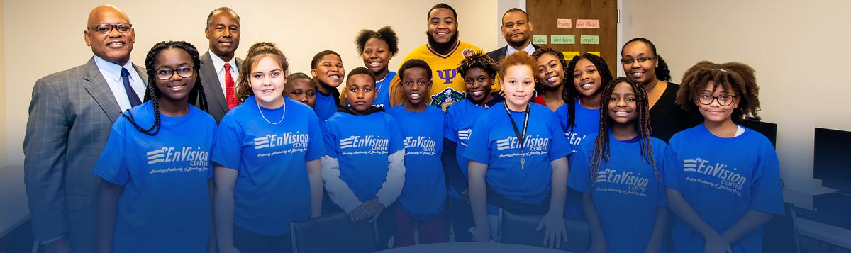 Photograph of Secretary Dr. Ben Carson with thirteen youth wearing EnVision Center t-shirts