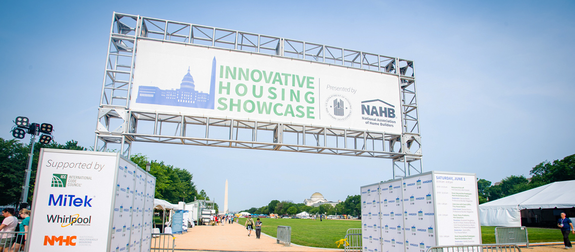 "A sign states ""Innovative Housing Showcase"" and bears the HUD and NAHB logos. Exhibits set up along the National Mall and the Washington Monument are visible in the background."