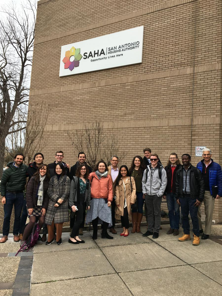 "Students in the four IAH finalist teams stand in front of a building bearing a sign that says: ""SAHA 