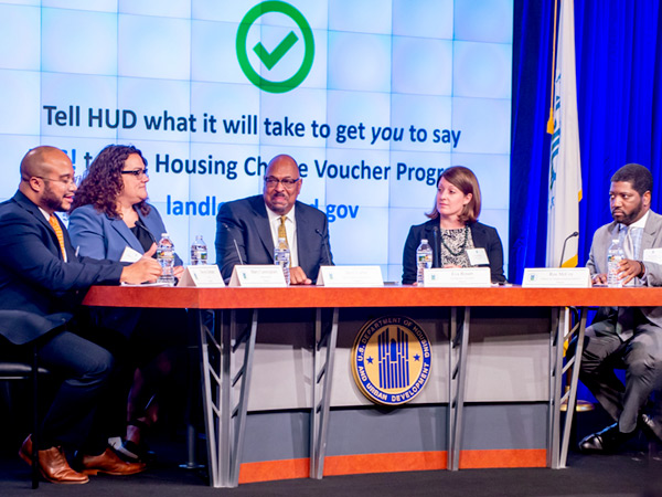 Steven Durham, director of Housing Voucher Programs in HUD's Office of Public and Indian Housing, sits left of four seated panelists at a table bearing the HUD logo.