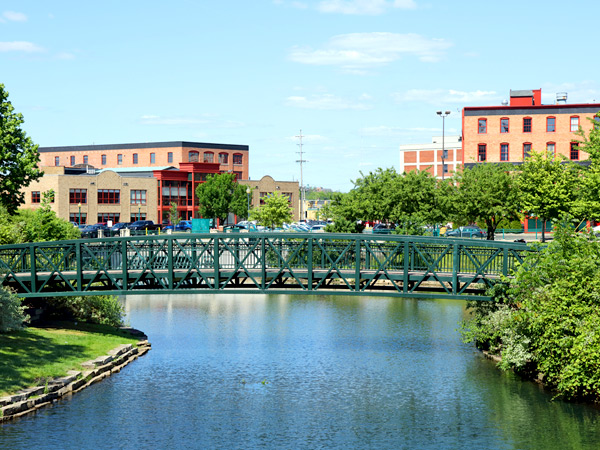 Downtown Kalamazoo, Michigan. A bridge over water is visible in the foreground, and multistory buildings and trees are visible in the background.