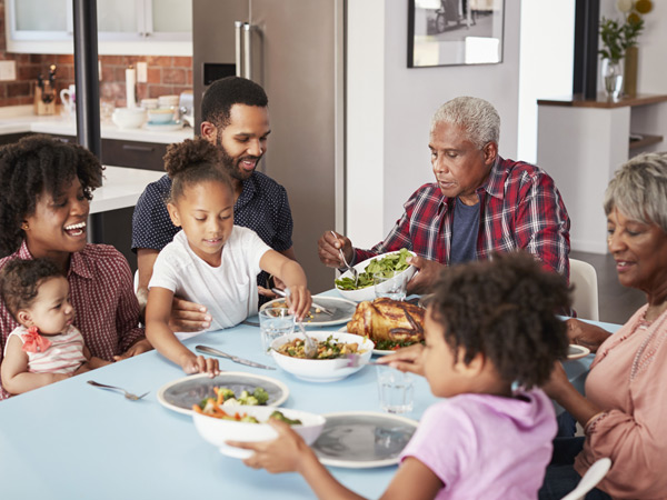 A multigenerational family, including two grandparents, two parents, and three children, are seated around a dinner table with food.
