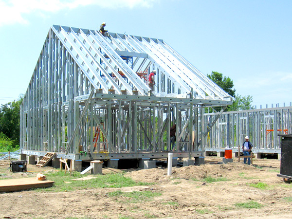 Photograph of workers constructing a steel frame of a home with a gable roof.