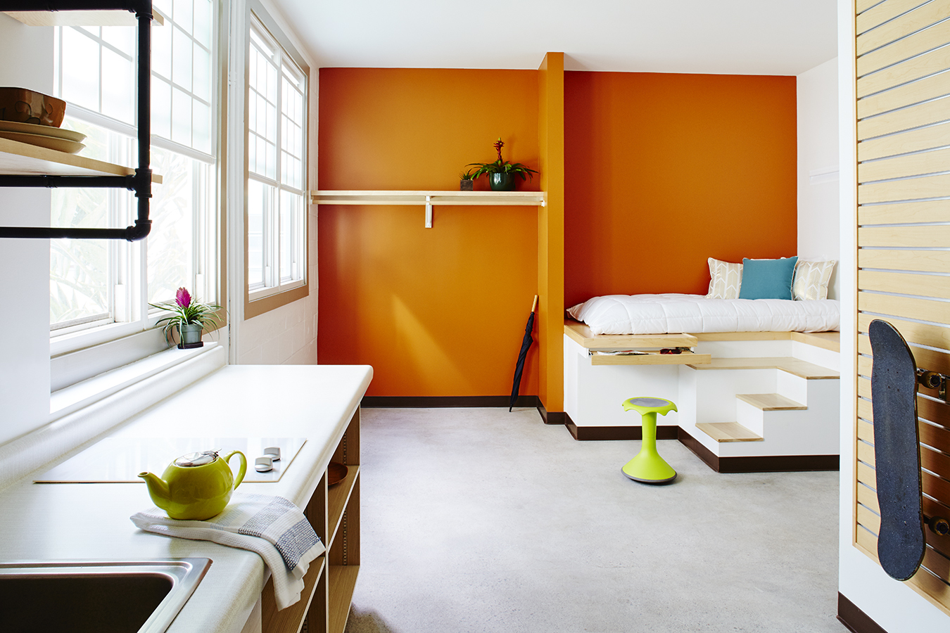 Photograph of the interior of an apartment, showing a small kitchenette, a bright orange wall, and a built-in platform bed.