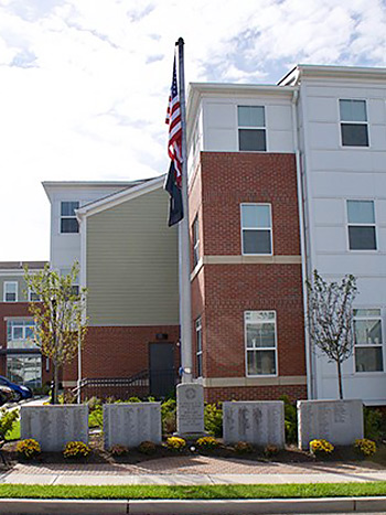Five memorial stones with a flagpole in front of a three-story apartment building.