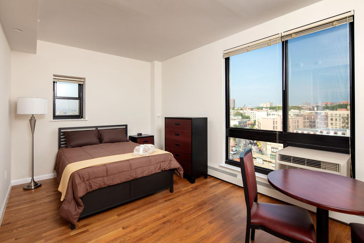 Image of a studio apartment with bed and small dining table.