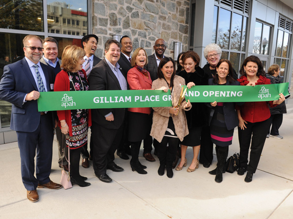 Photograph of group of people in front of a building holding a banner that says Gilliam Place Grand Opening being cut by one person in the center with scissors.