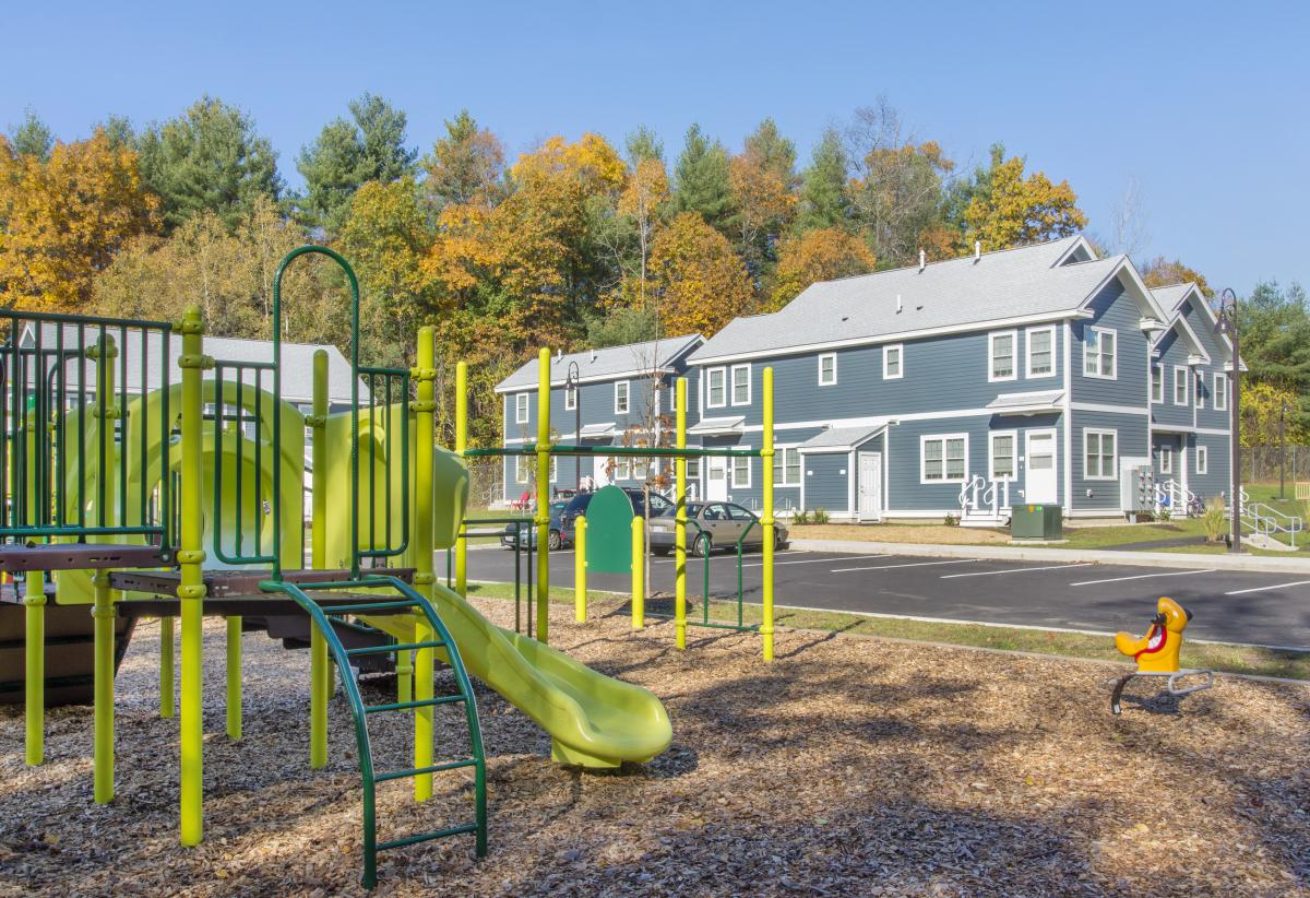 Image of two-story, colonial-style apartment buildings with playground structure in the foreground.