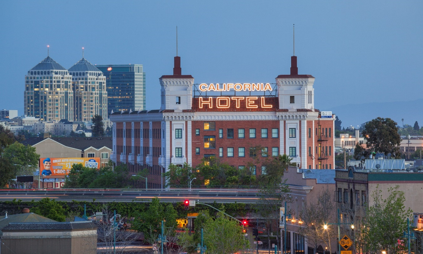 "A photo of the front and side façade of a red brick and white stucco building topped by a marquee with a lit sign that reads ""California Hotel."" A freeway is in the foreground."