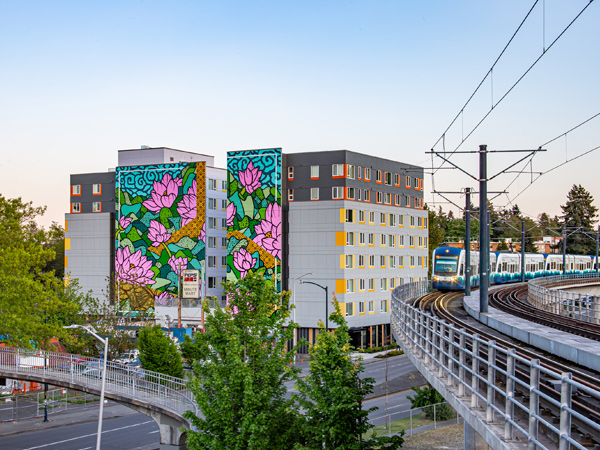 Image of a new apartment building with a multi-story mural painted on one side.