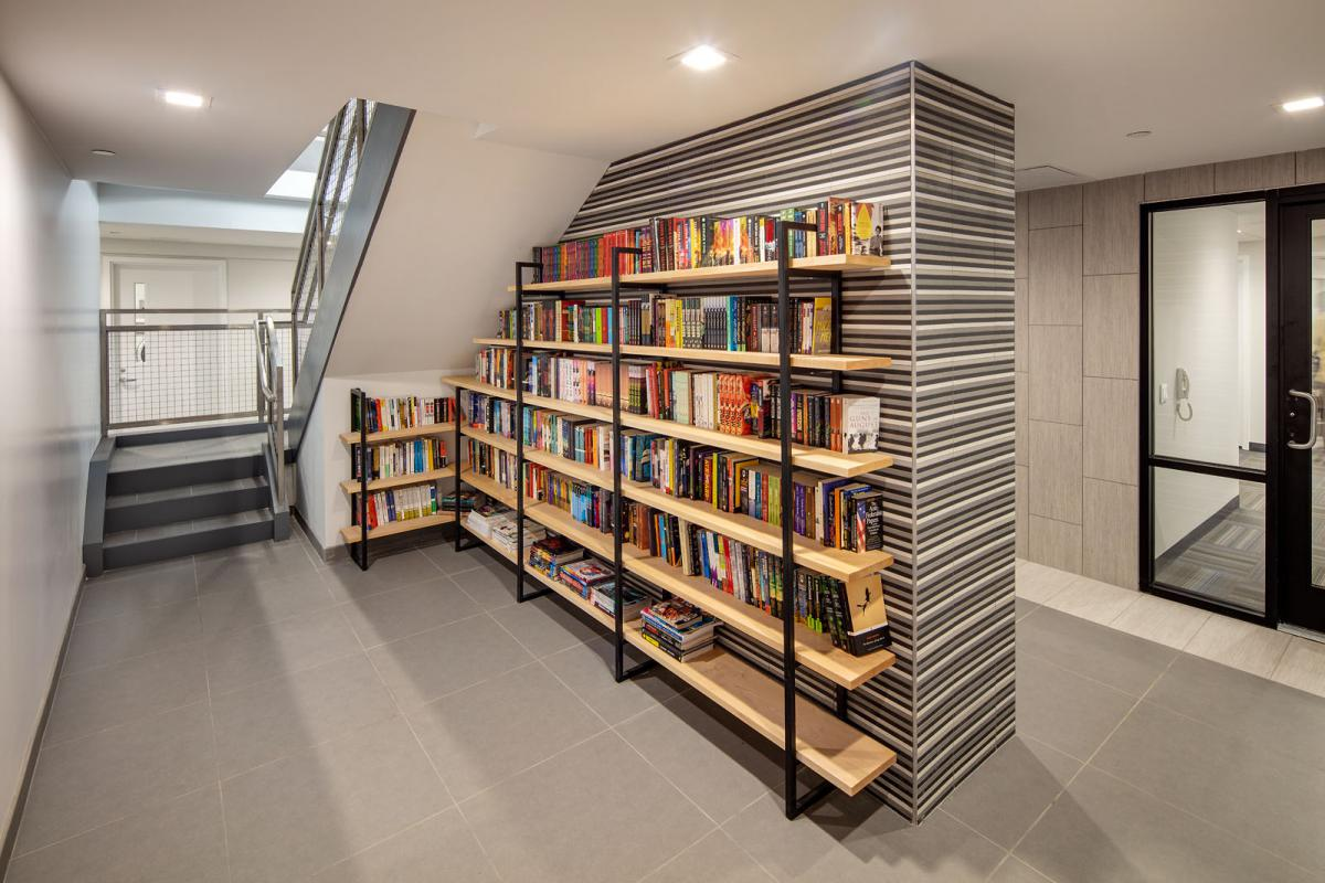 Image of books on shelves tucked under an apartment building staircase.