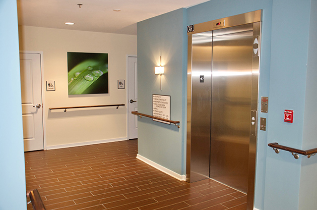 Picture of an apartment building hallway, showing an elevator, handrails along the walls, and handicap accessible bathrooms.