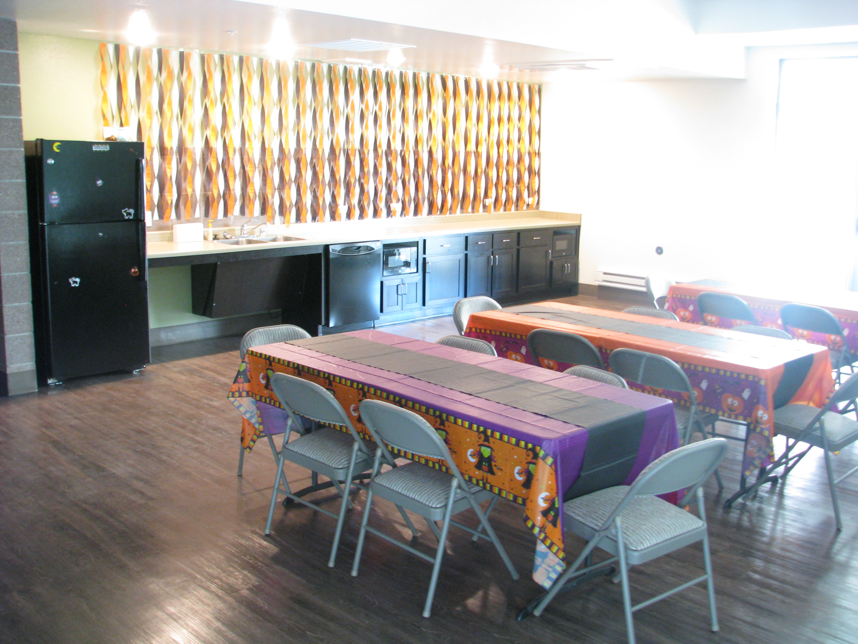 Photograph of a room with a kitchenette and several tables and chairs with Halloween-themed paper tablecloths.