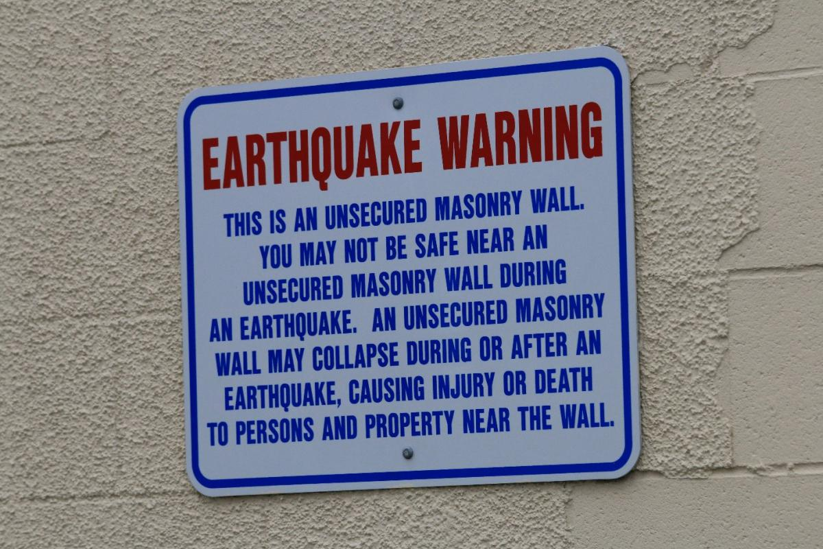 A sign board affixed to a wall showing an earthquake warning.