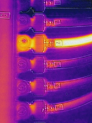 Thermal image of a plumbing manifold and tubing, where the tube through which hot water is flowing is visible.