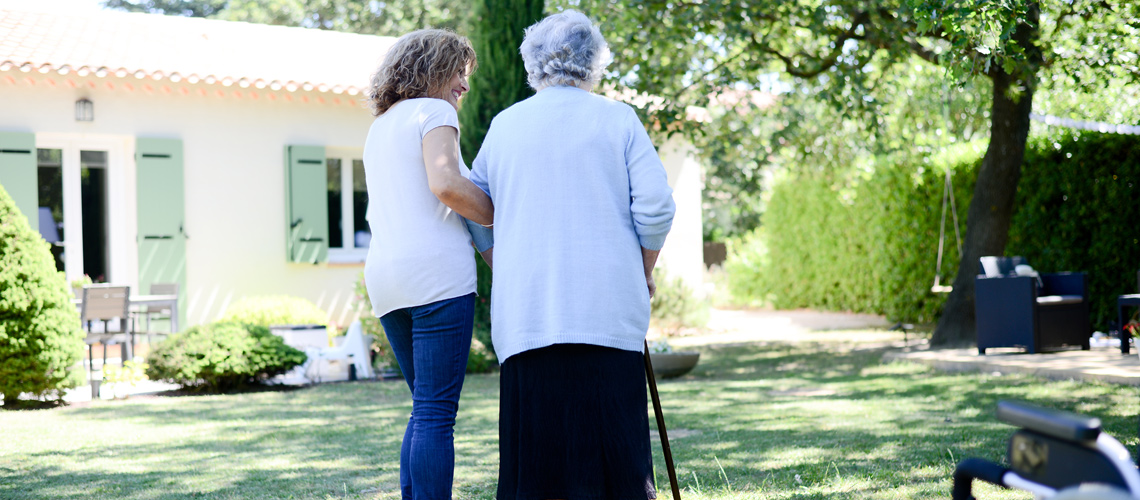 Photograph of a younger woman assisting an older woman walking with a cane in the backyard of a single-family home.