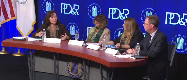 Image showing four individuals, Principal Deputy Assistant Secretary of HUD's Office of Community Planning and Development Harriet Tregoning and three panelists, seated at a table bearing the HUD logo. An image with the HUD and PD&R logos is visible on a screen behind the table.