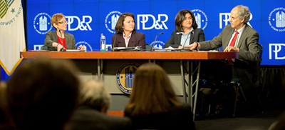Image showing four individuals, Assistant Secretary for Policy Development and Research Katherine O'Regan, HUD senior leadership, including Harriet Tregoning, Lourdes M. Castro Ramirez, and Edward L. Golding seated at a table bearing the HUD logo. An image with the HUD and PD&R logos is visible on a screen behind the table.