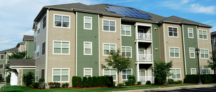 Photograph of the rear façade of a three story multifamily residential building featuring solar panels on the roof.