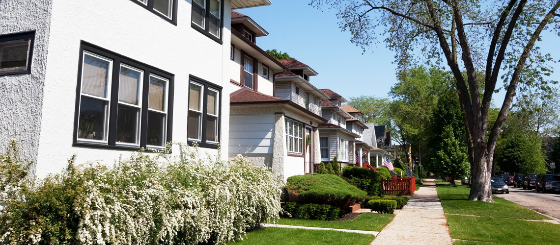 Image of single family homes and a sidewalk lining a street in the Albany Park neighborhood of Chicago, IL