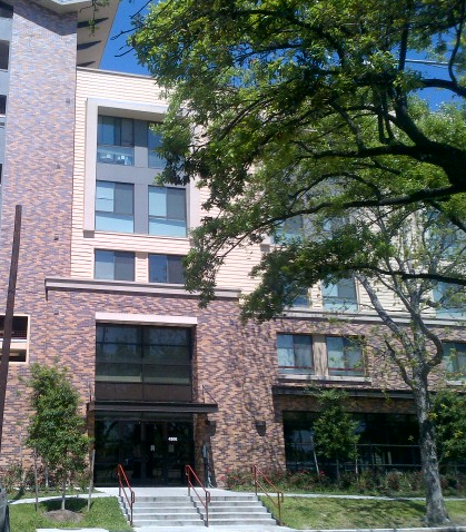 Photograph of the entrance to a five-story brick, metal, and vinyl-sided apartment building.