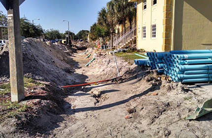 Photograph of a shallow trench running along a street in front of several residential buildings, with plastic pipes stored nearby.
