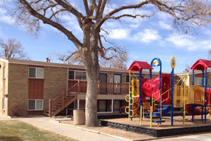 Photograph of multiple two-story residential buildings located adjacent to a small playground.